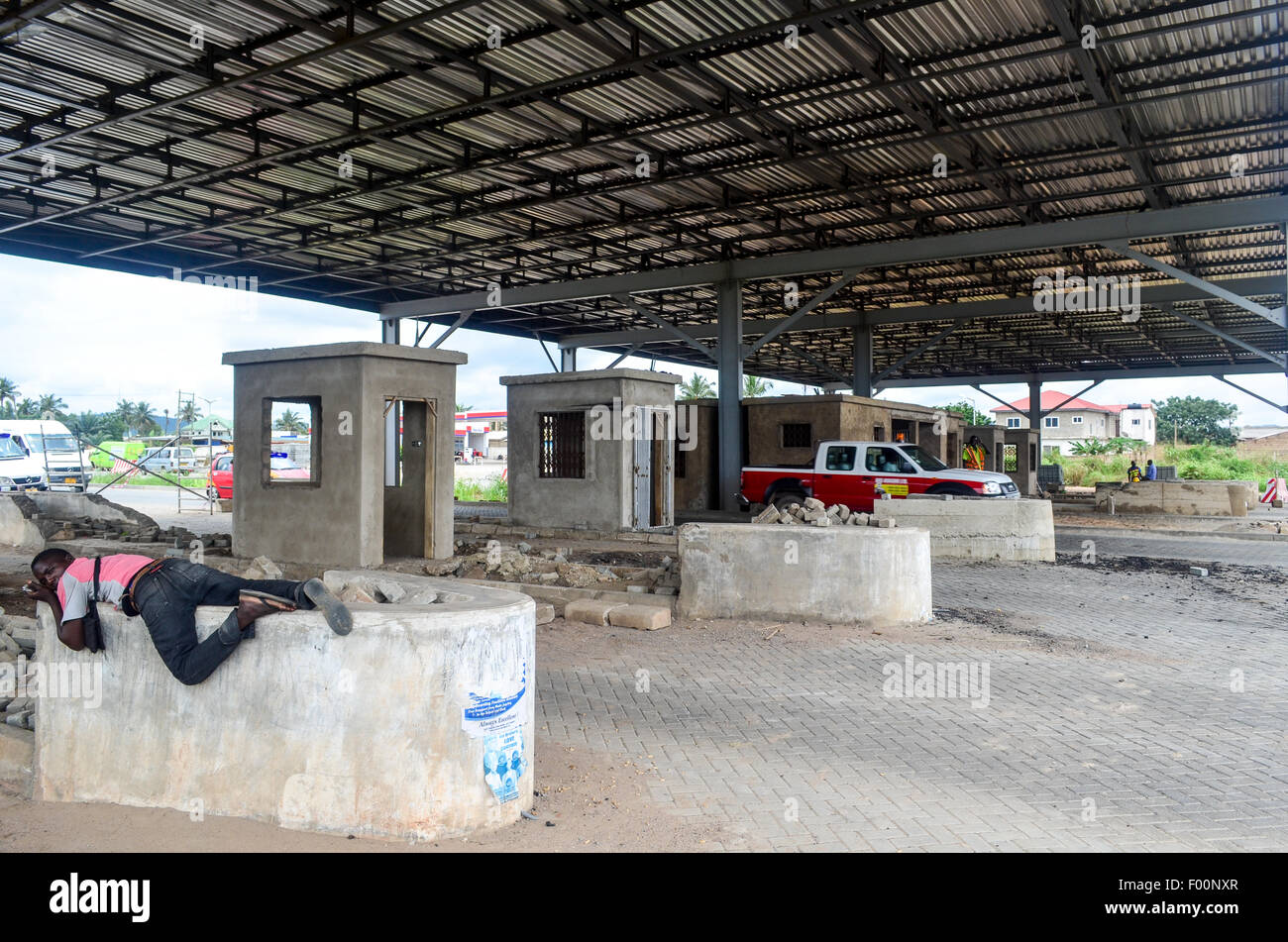 New highway toll in construction at the entrance of Accra, Ghana, and man sleeping - Stock Image