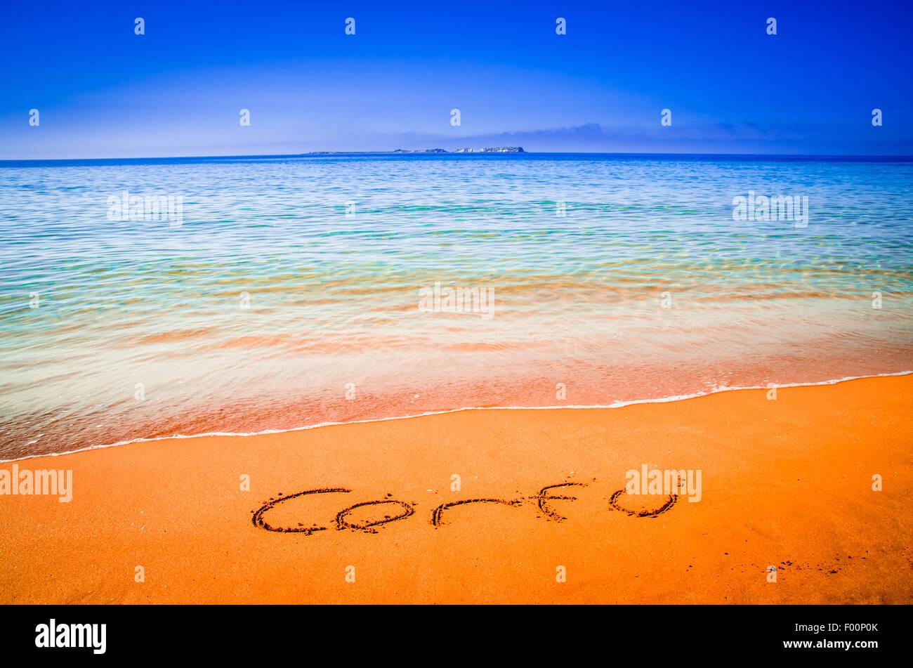 Corfu word written on a sandy golden beach, Greece. Selective focus. - Stock Image