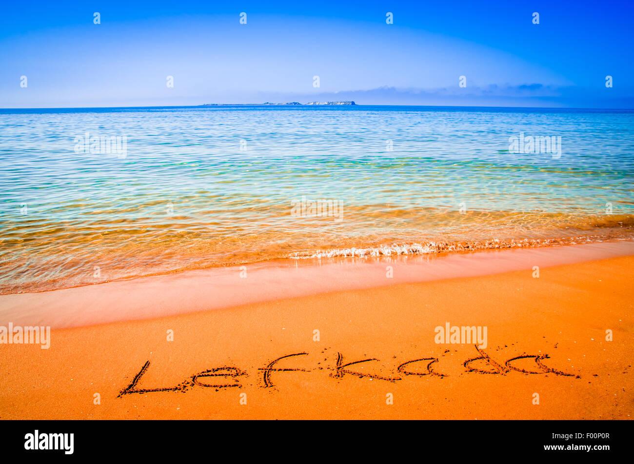 Lefkada word written on a sandy golden beach, Greece. Selective focus. - Stock Image
