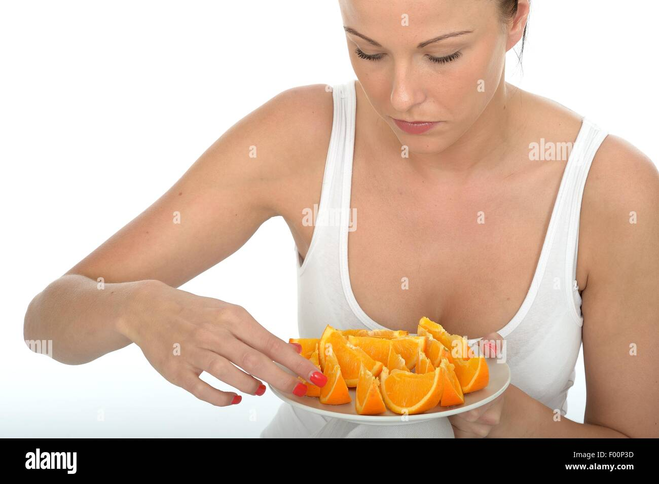 Attractive Happy Healthy Young Woman Holding a Plate of Fresh Cut Oranges - Stock Image