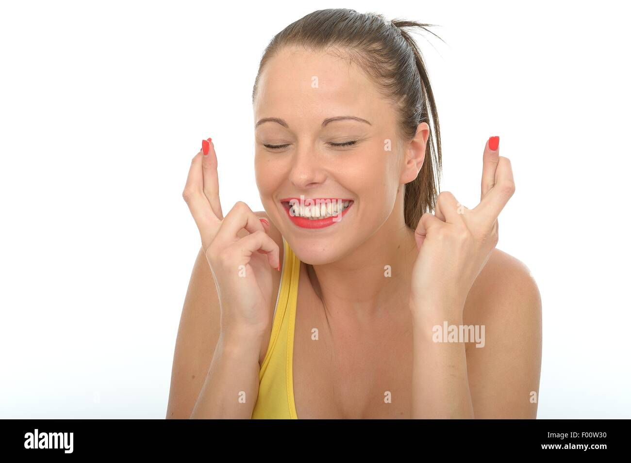 Portrait of a Happy Excited Young Woman With Her Fingers Crossed - Stock Image