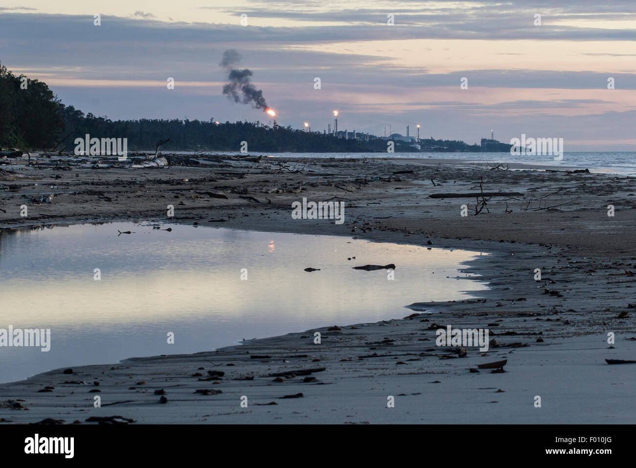 Gas flare at natural gas complex, as viewed from a nearby beach. - Stock Image