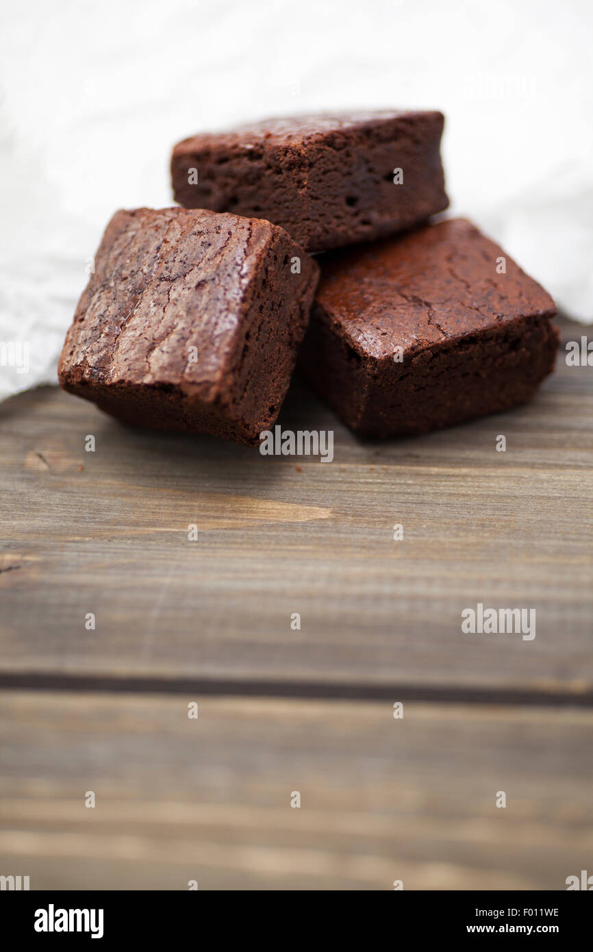 Stack of fresh and indulgent chocolate brownies on a textured background - Stock Image
