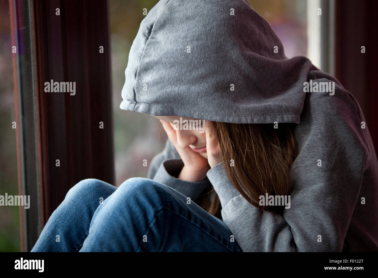 Sad girl in hooded top, sitting with head in hands in despair - Stock Image