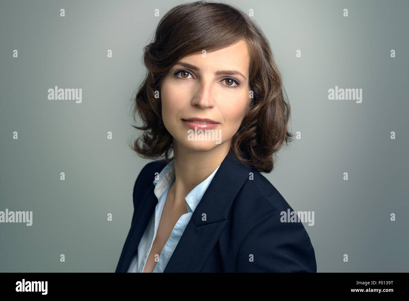 Attractive businesswoman with curly brown hair wearing a stylish jacket standing sideways looking at the camera - Stock Image