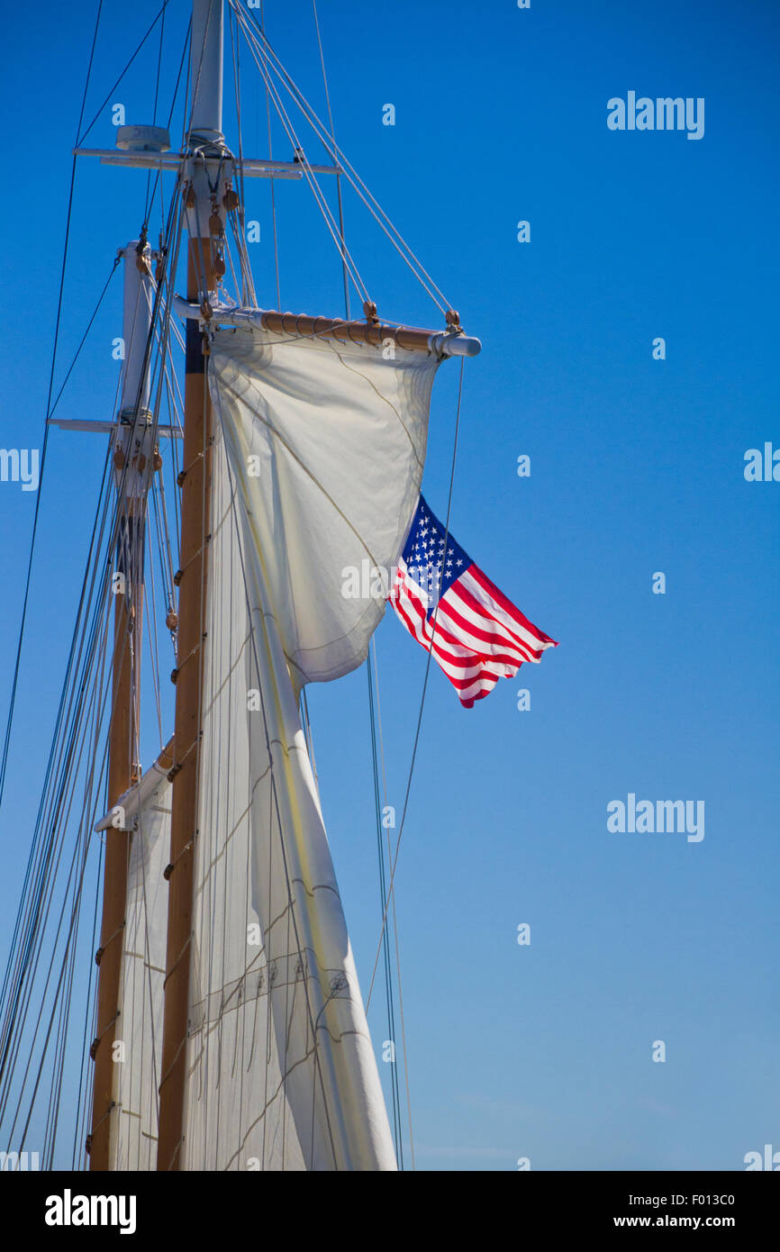 Double Masted Wooden Sail boat with an American Flag waving in the breeze - Stock Image