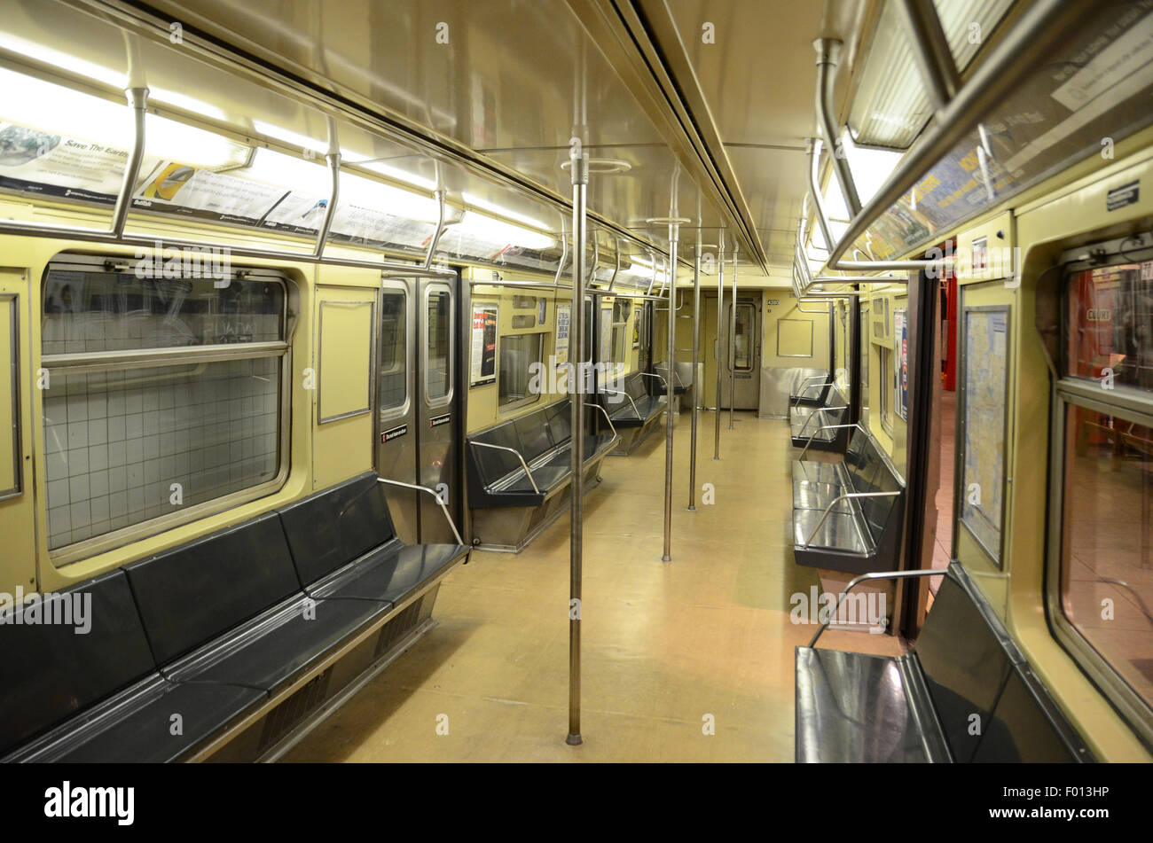 New York Transit Museum carriage subway vintage subway 1968; yellow livery vintage adverts hand rails grey gray - Stock Image