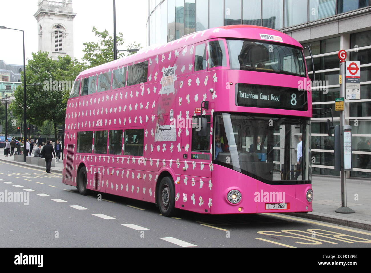 A PINK NEW ROUTEMASTER BUS IN LONDON ADVERTISING PROPER CORN - Stock Image