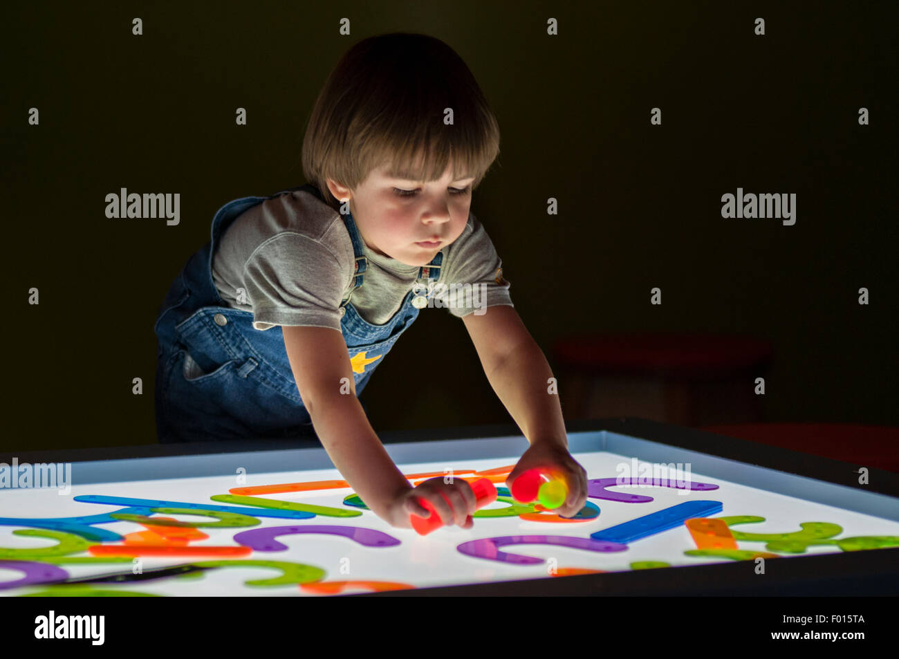 Four Year Old Boy Playing with Colored Objects on Light Box at the Kentucky Science Center in Louisville Kentucky - Stock Image