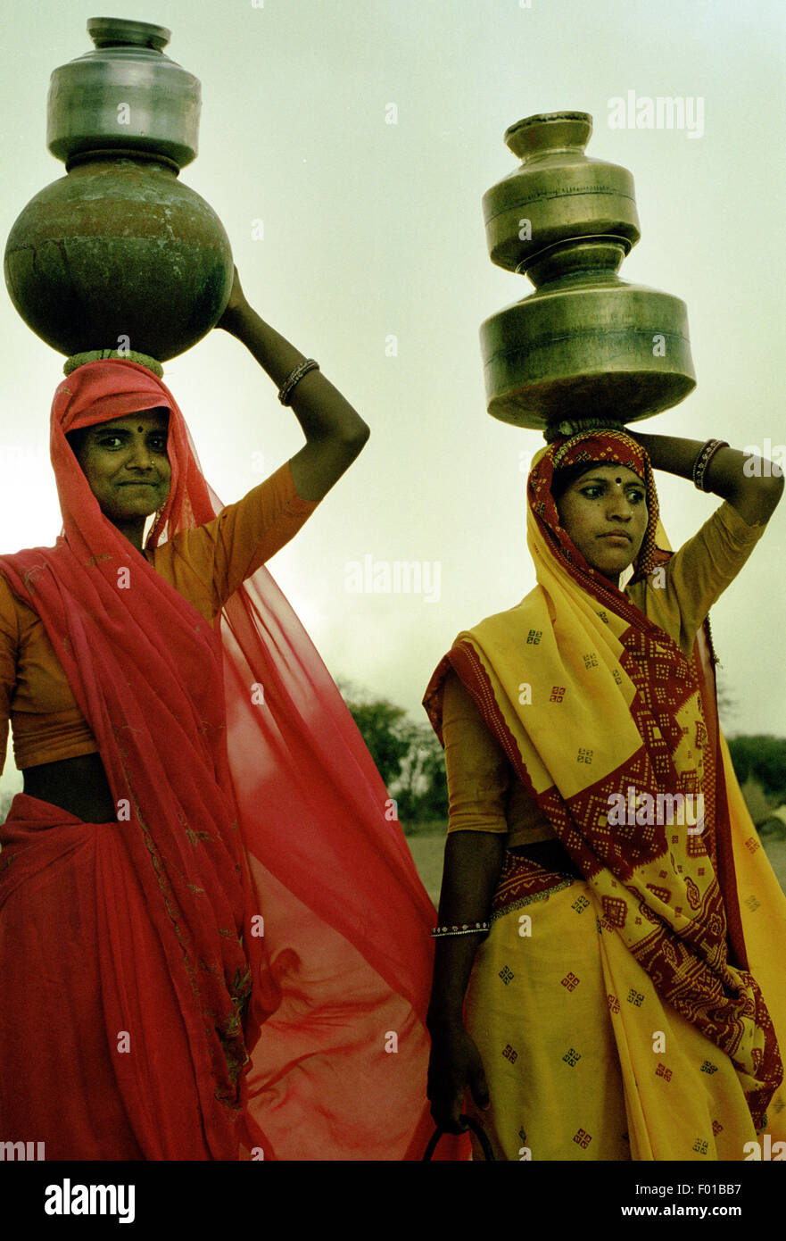 two indian women carrying water brian mcguire - Stock Image