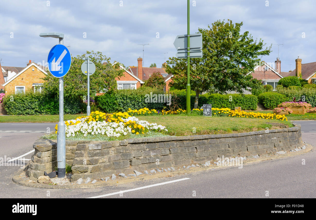 Flowers on an island at a road junction in West Sussex, England, UK. - Stock Image