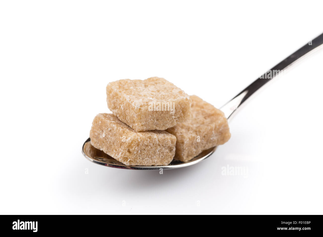 Cubes of brown sugar on a metal spoon - Stock Image