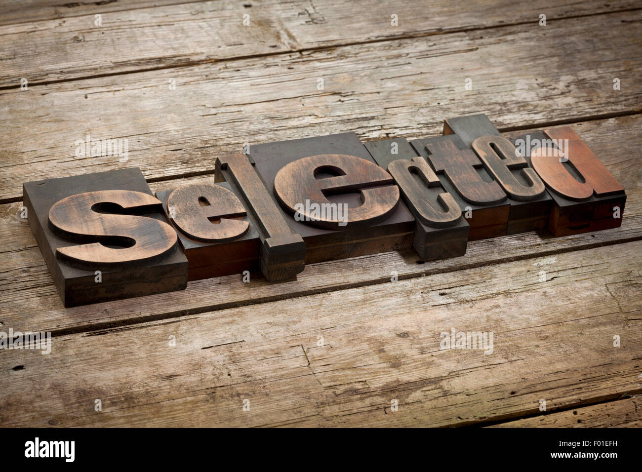 selected, word written with vintage letterpress printing blocks, angled view, rustic wooden background - Stock Image