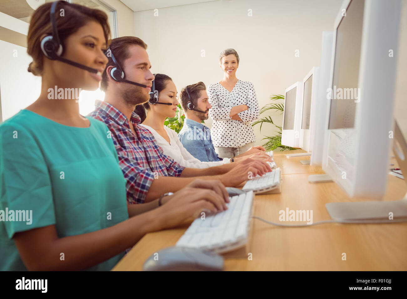 Manager supervising work in call center - Stock Image