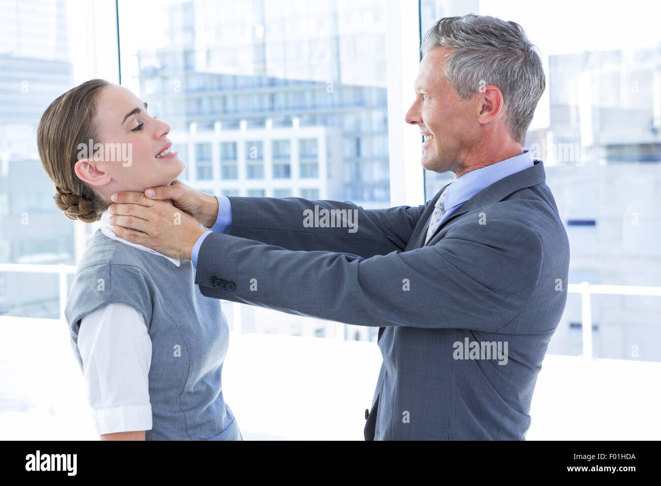 Businessman trying to smother his colleague - Stock Image