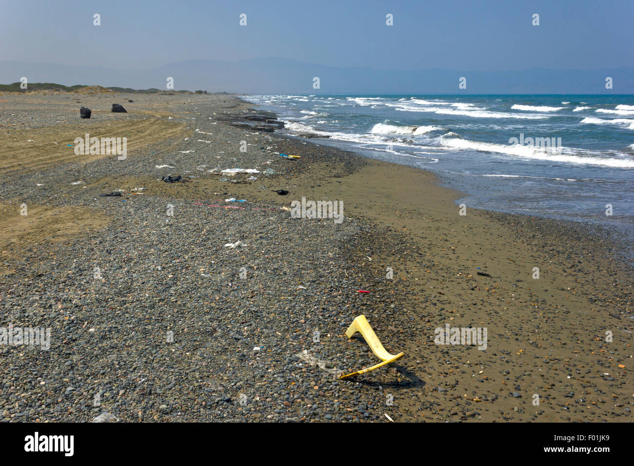 Pebbly  Mediterranean beach showing the ocean and plastic pollutants - Stock Image