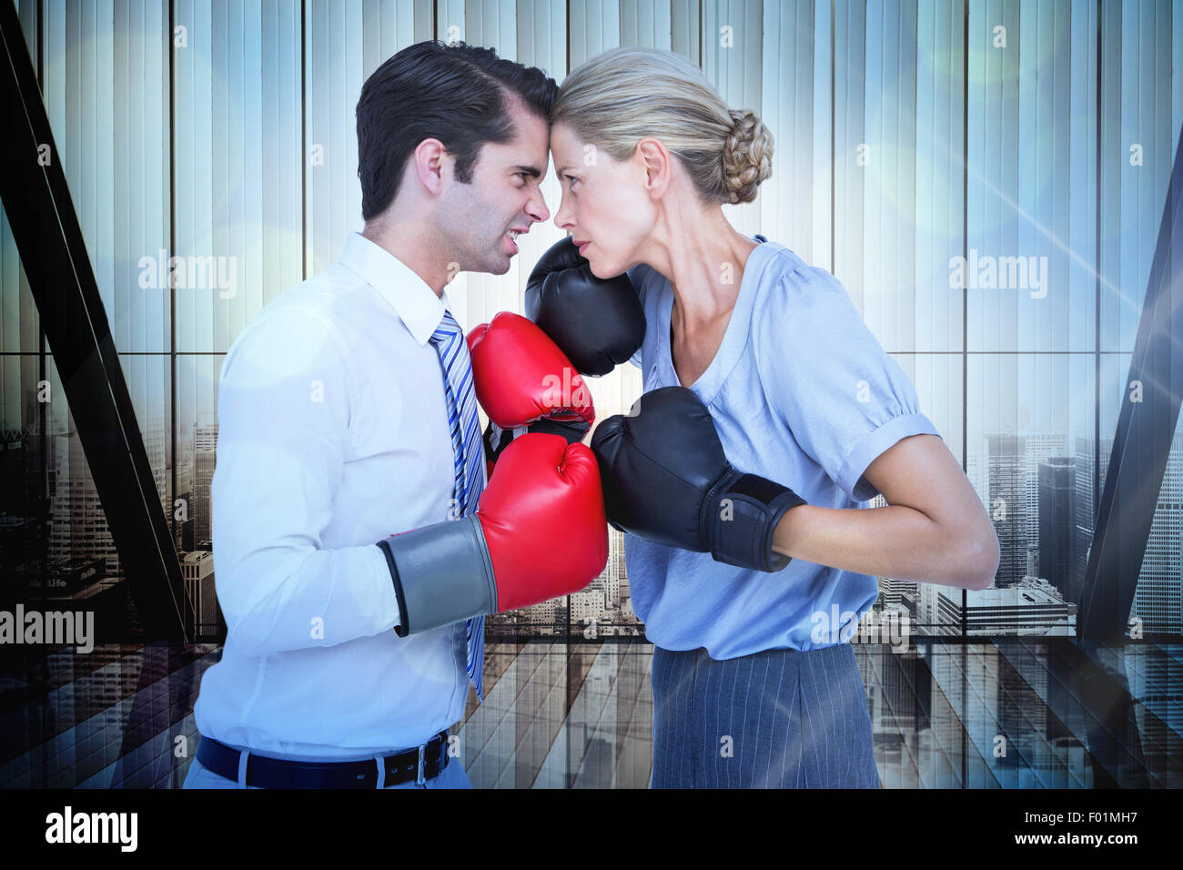 Composite image of business people wearing and boxing red gloves - Stock Image