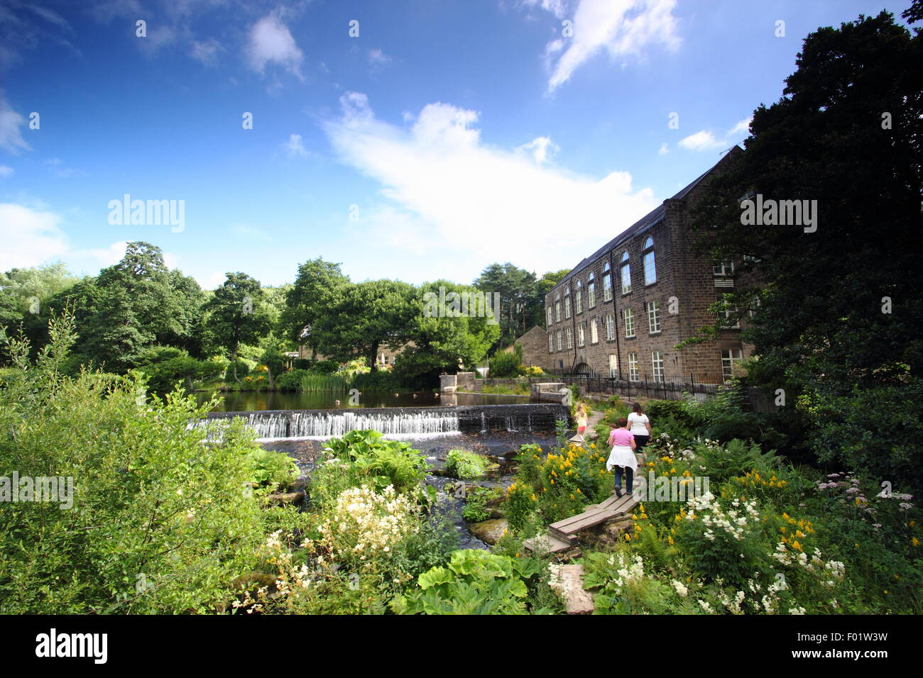 People cross the public footbridge across the River Derwent by Bamford Mill and weir in the Peak District National Stock Photo