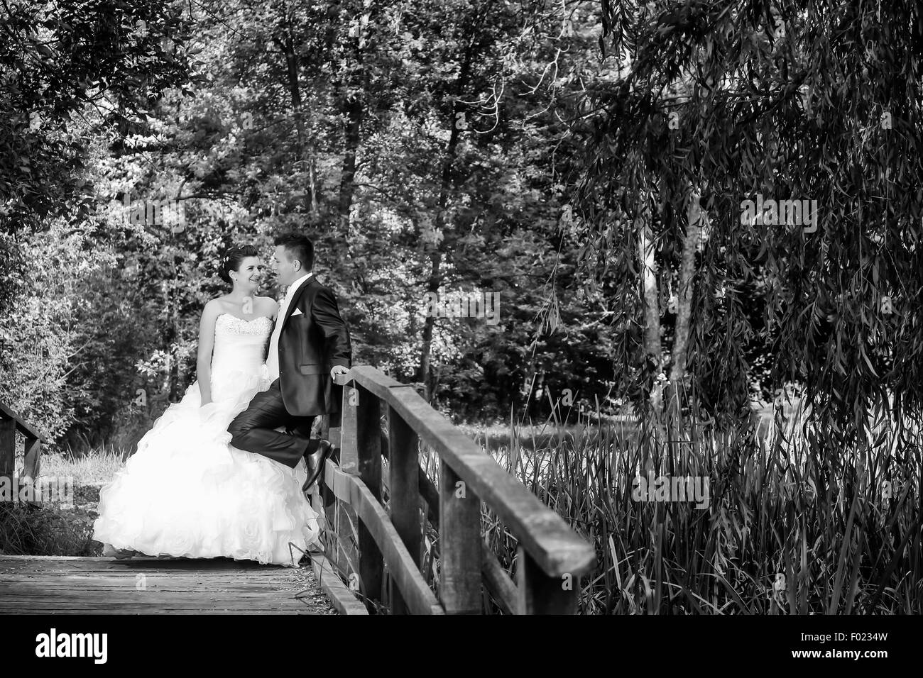 The bride and groom standing on a wooden bridge in nature and  looking at each other while the groom is leaning - Stock Image