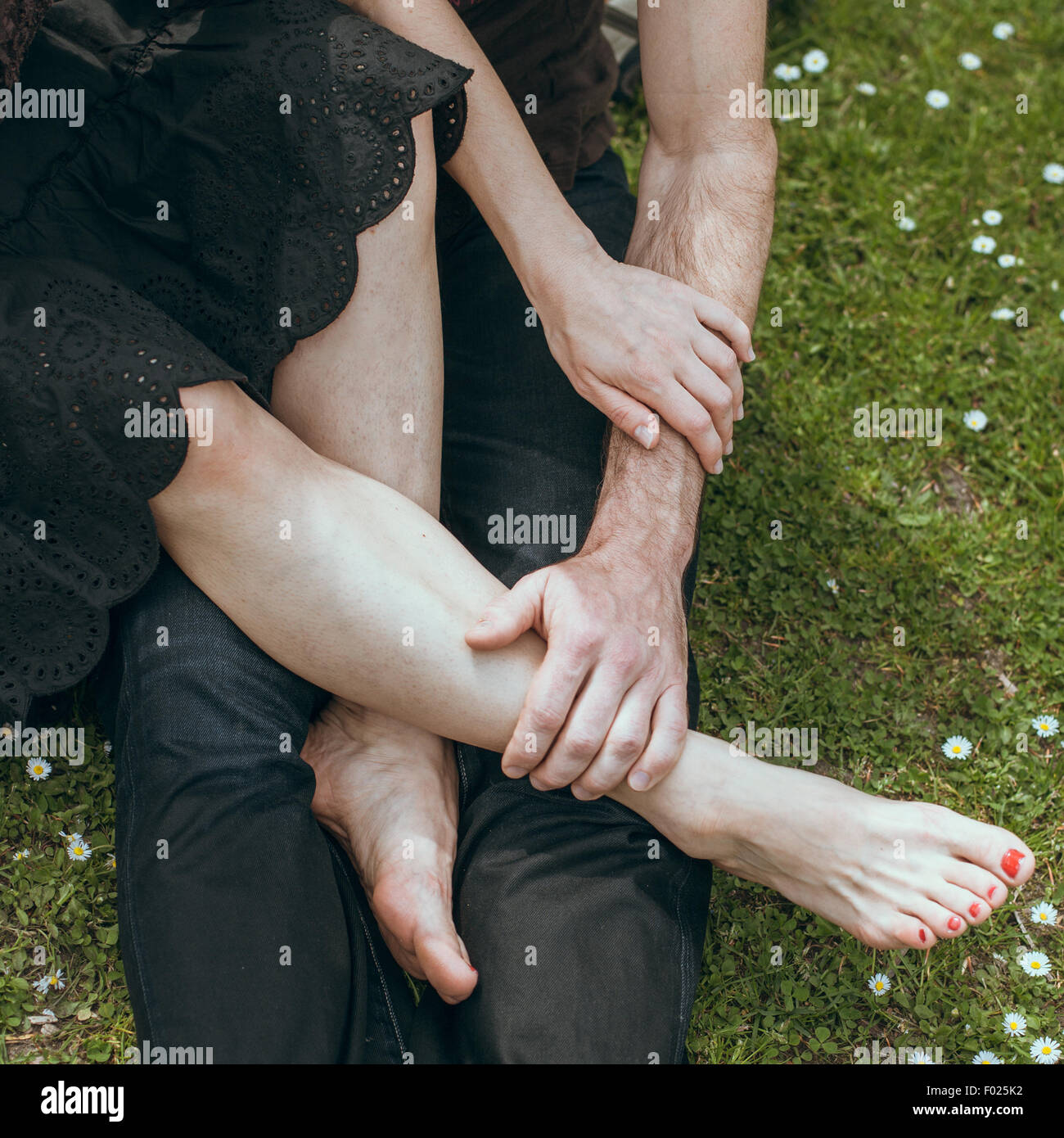 Close up of mature man holding a mature woman's feet in his hand - Stock Image