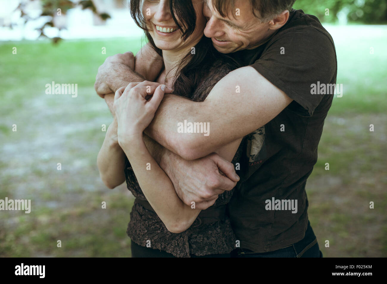 Mature man embracing mature women from behind Stock Photo