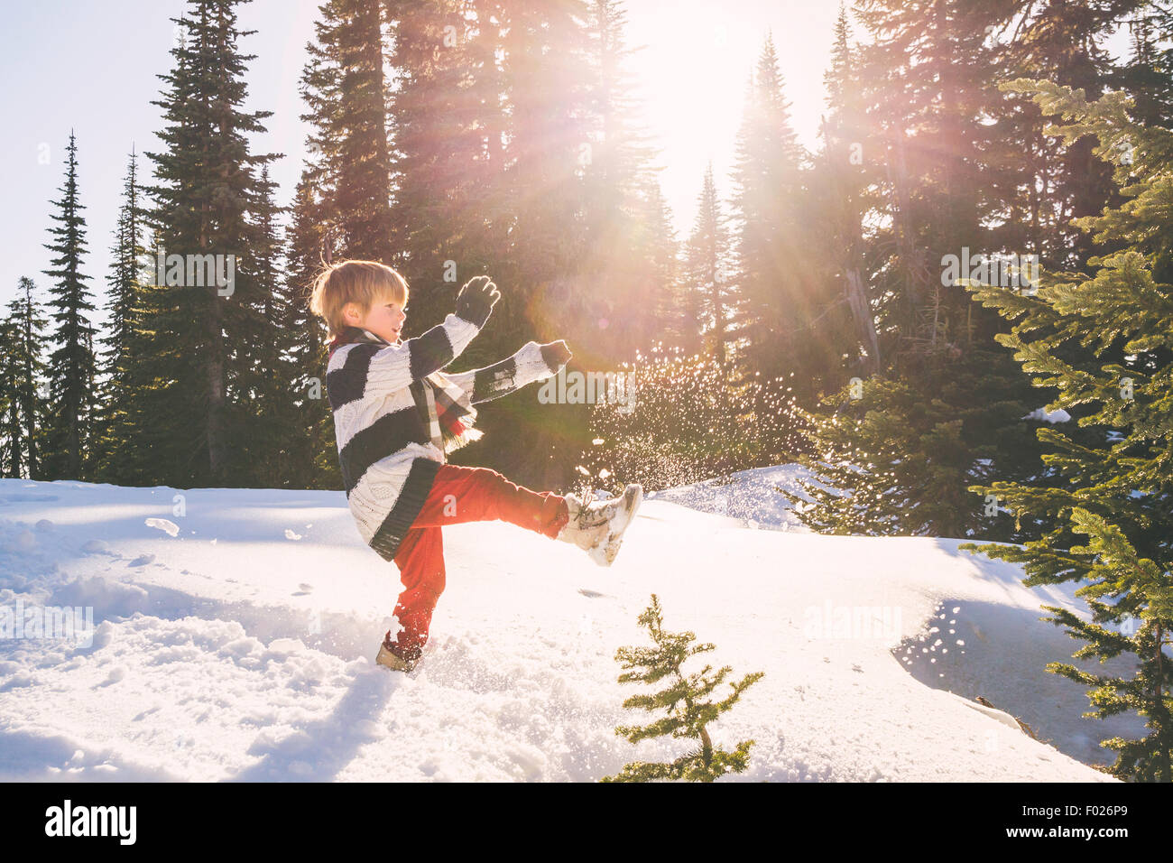 Boy kicking snow in the air - Stock Image