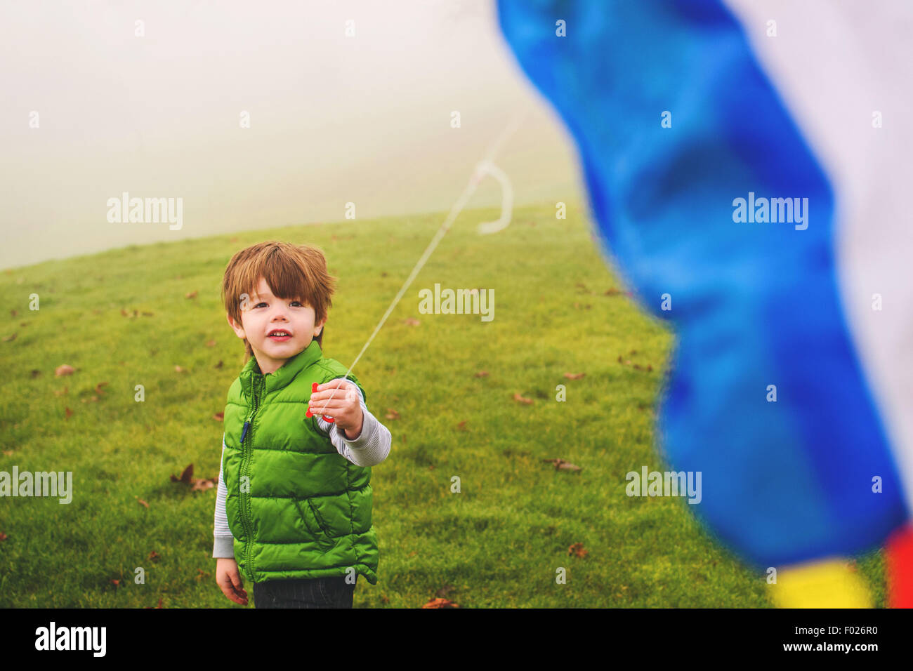 Boy holding a kite in the fog - Stock Image