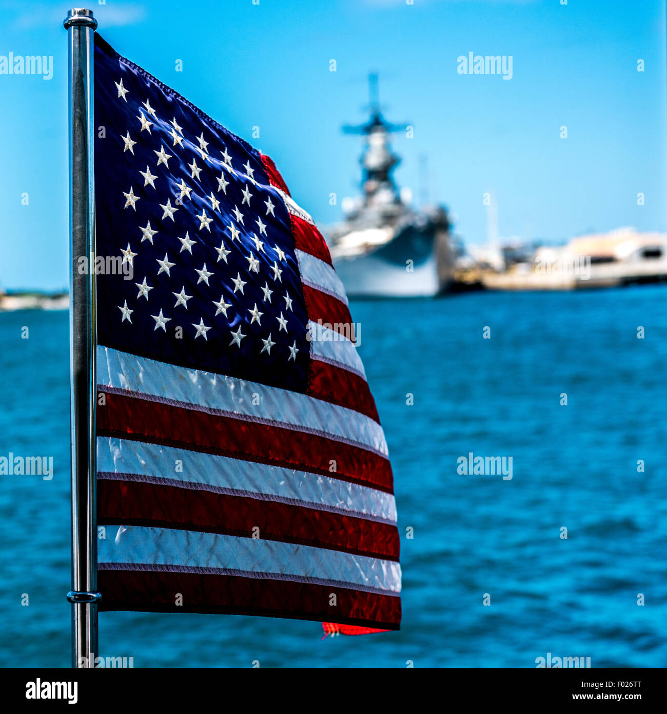 American flag blowing in the wind with navy ship in the background, Hawaii - Stock Image