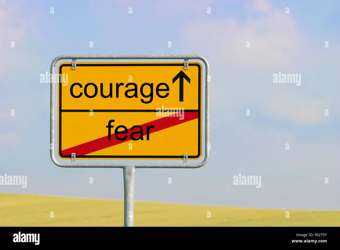 Yellow town sign with text 'fear courage' - Stock Image