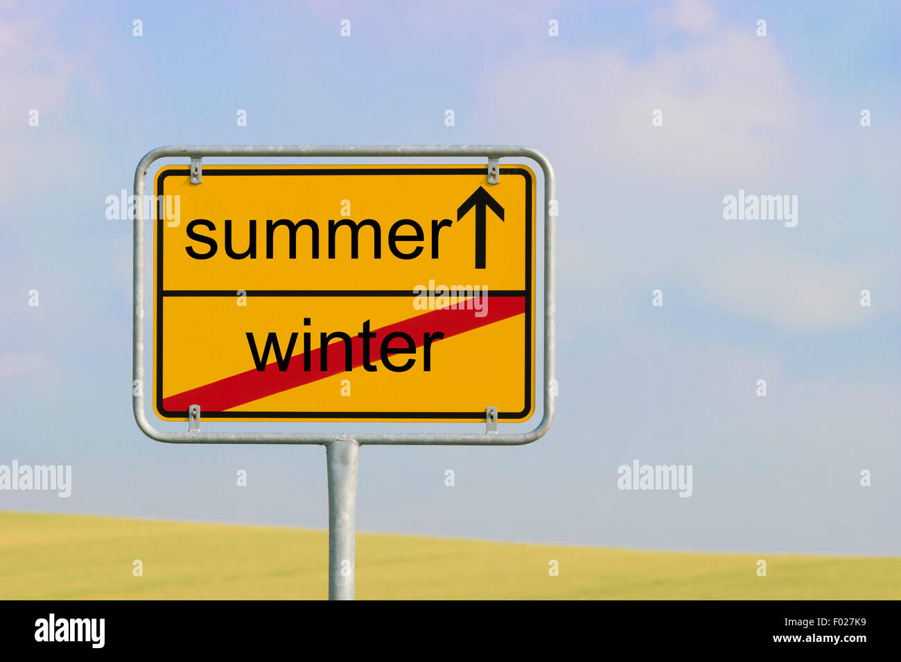 Yellow town sign with text 'winter summer' - Stock Image