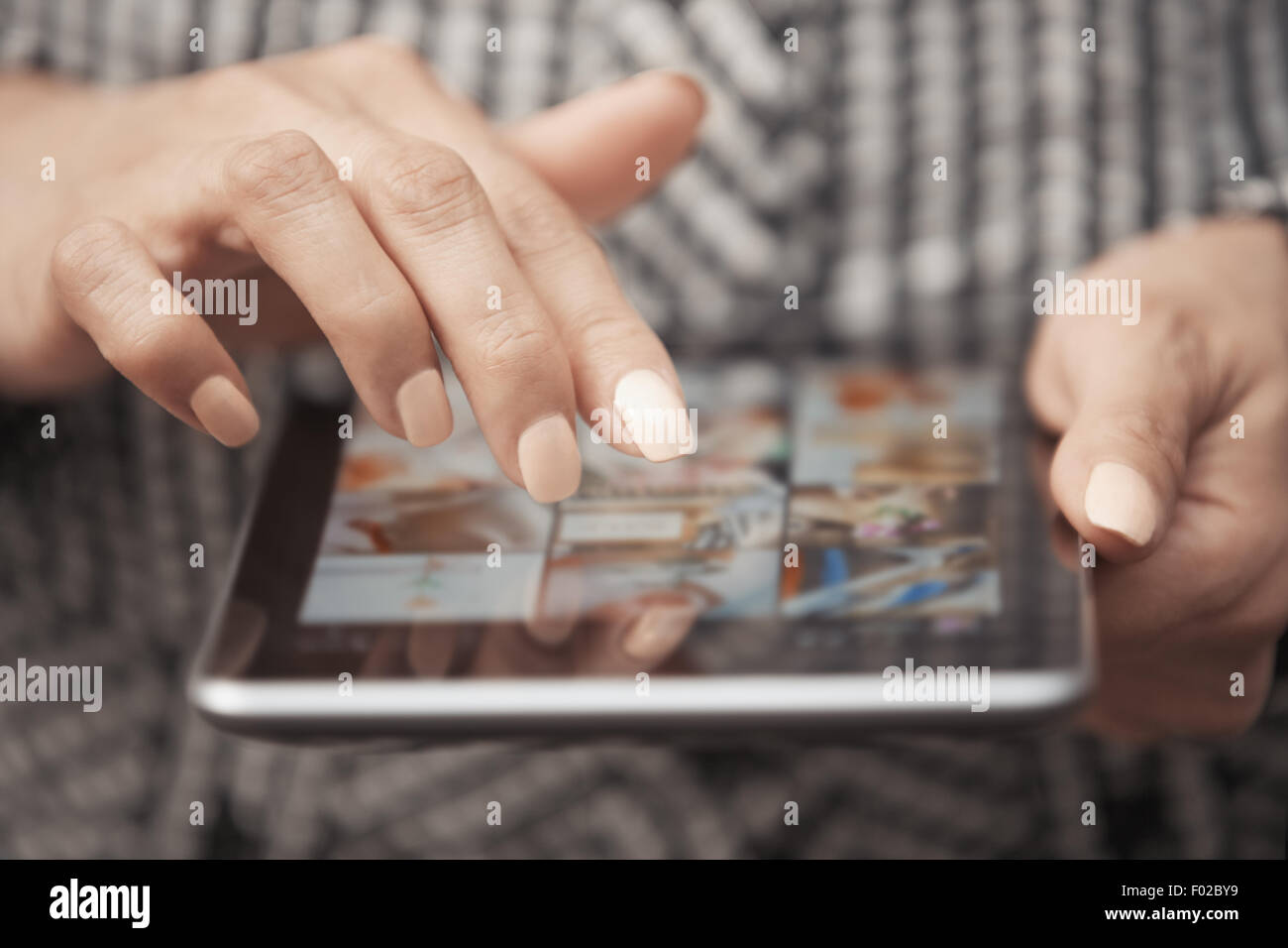 Woman with tablet computer looking digital photos - Stock Image