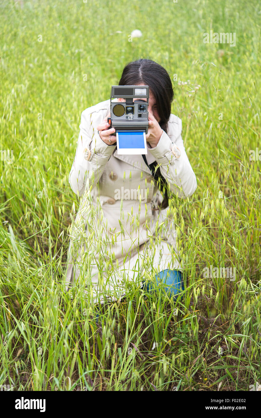 Woman taking a photo with a vintage instant camera - Stock Image