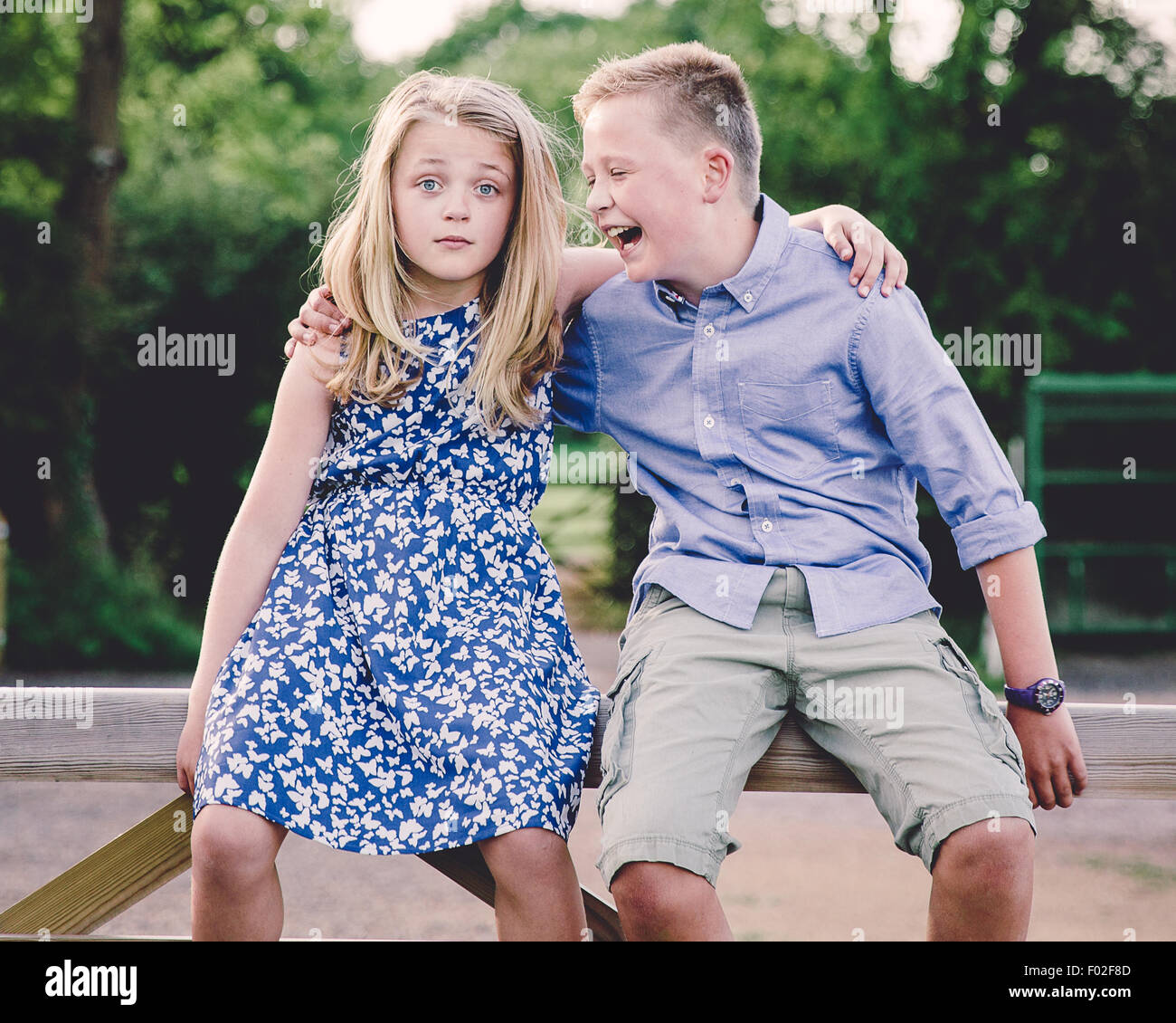 Boy and girl sitting on wooden gate with their arms around each other - Stock Image