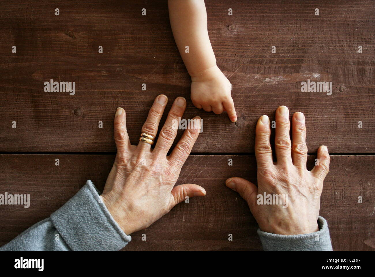 Baby boy's hand pointing at grandmother's hands - Stock Image