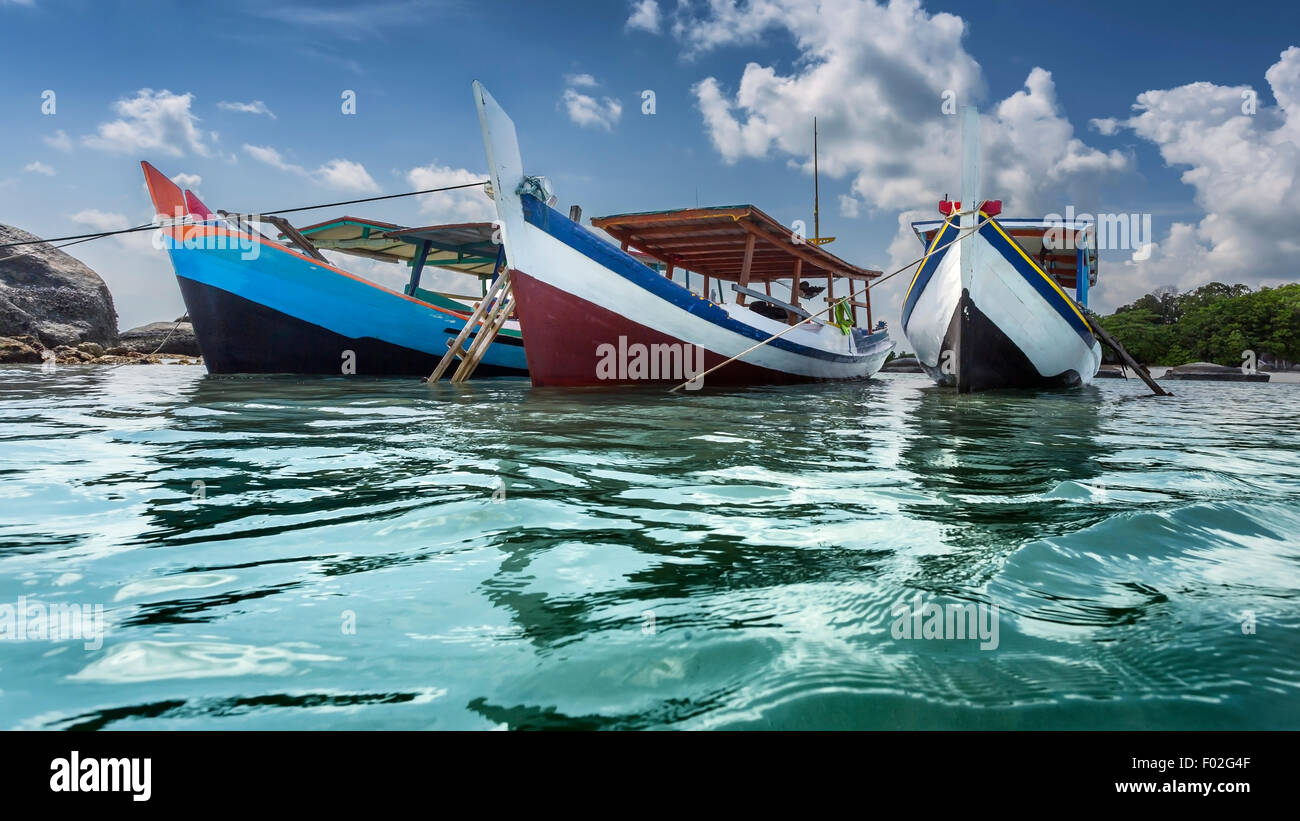 Three boats anchored at beach, Belitung Island, Indonesia - Stock Image