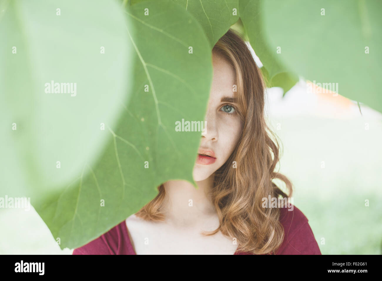 Portrait of a young woman with face obscured by leaves - Stock Image