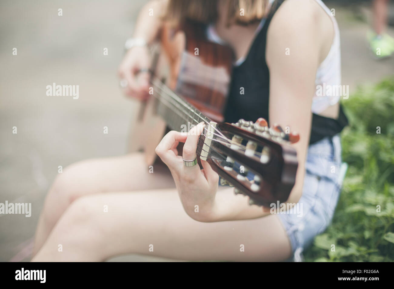 Close-up of a young woman playing the guitar - Stock Image