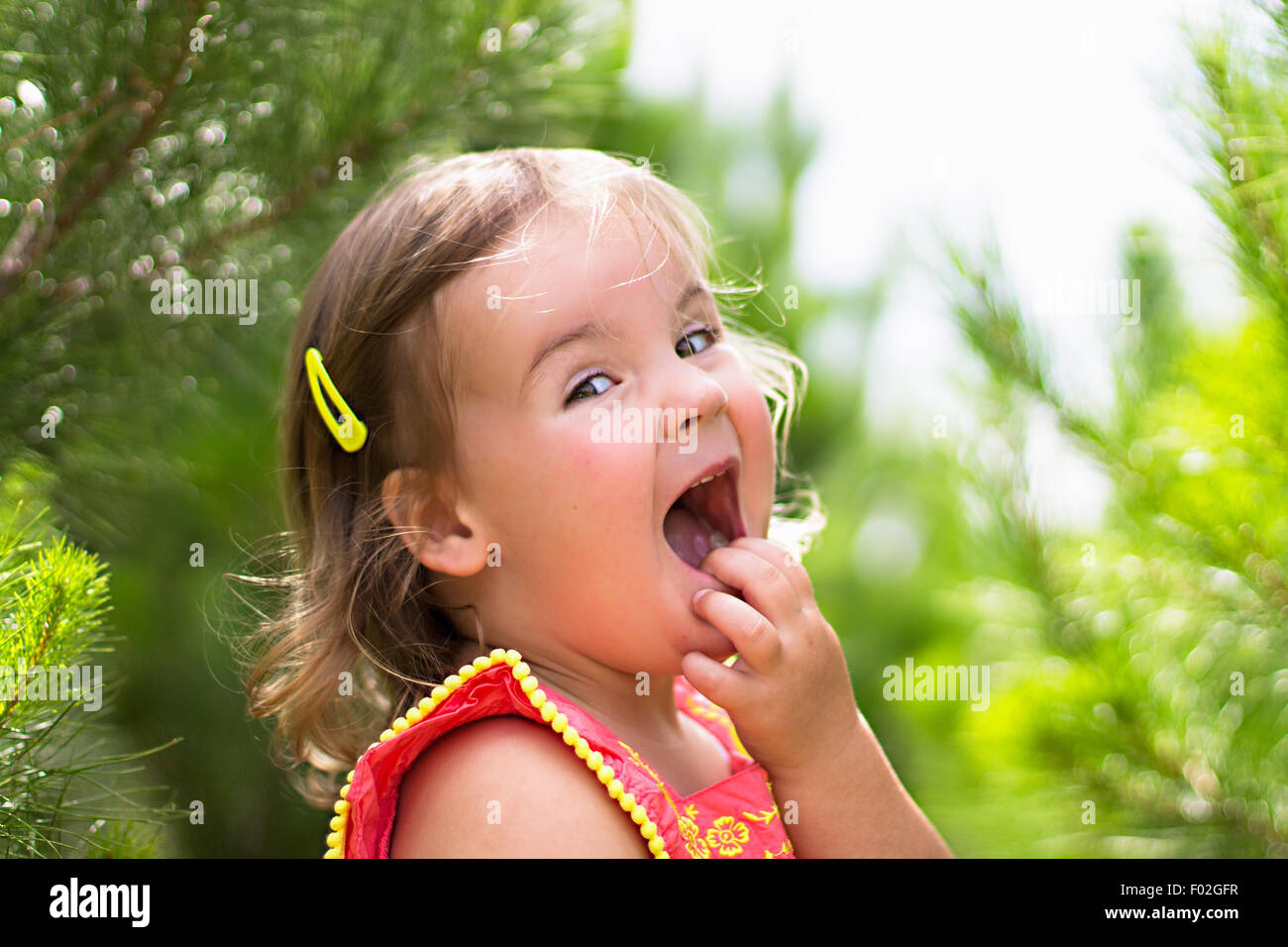 Girl with hand on face laughing Stock Photo