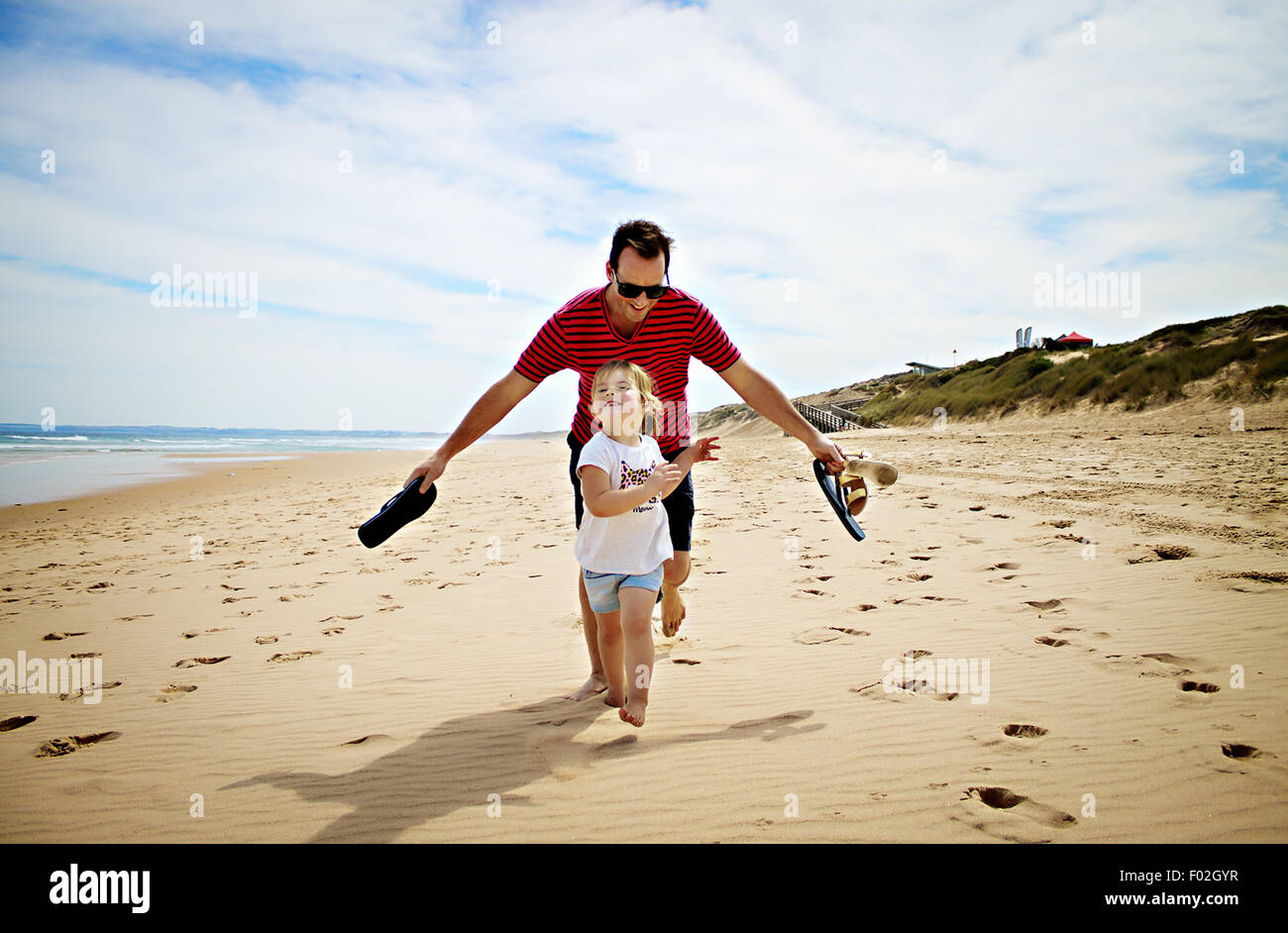 Father and daughter racing on the beach - Stock Image
