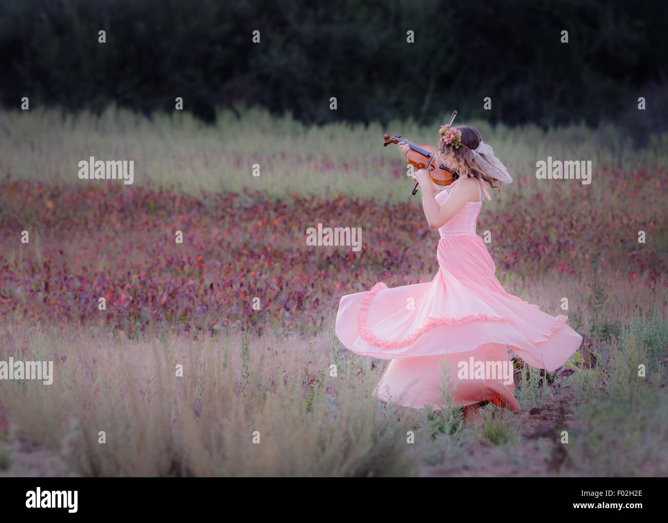 Girl dancing in a field whilst playing a violin - Stock Image