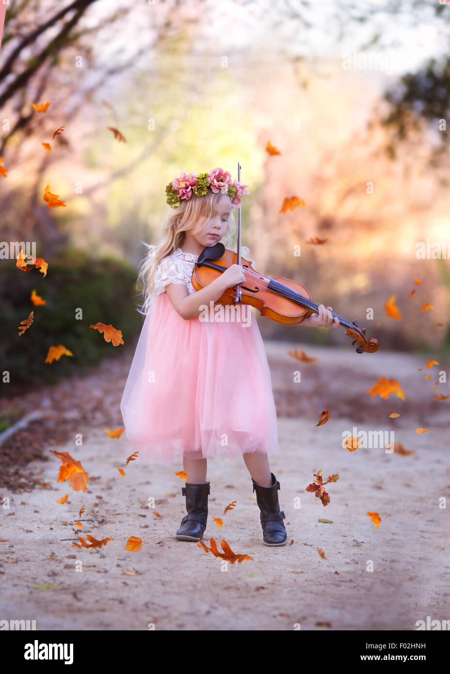 Girl standing in road playing the violin with leaves falling all around - Stock Image
