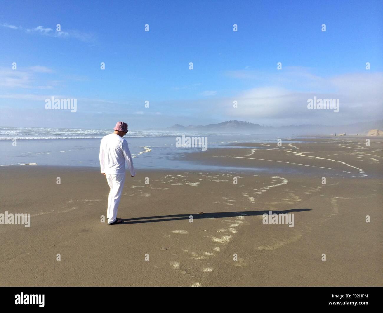 Man walking along the beach, Cannon Beach, Oregon - Stock Image