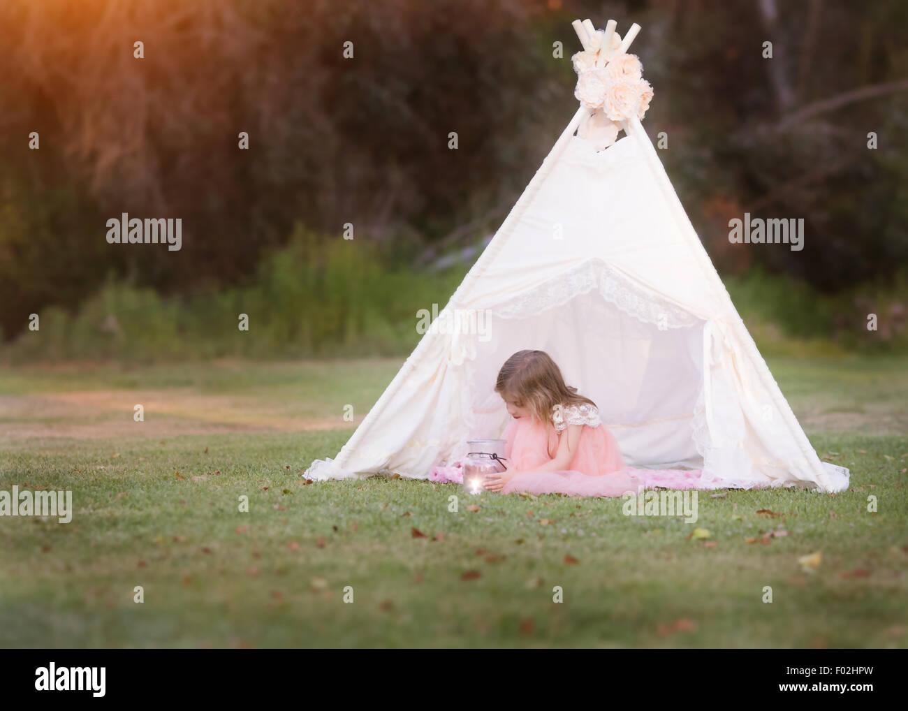 Girl sitting in a wigwam gazing into a lantern jar - Stock Image