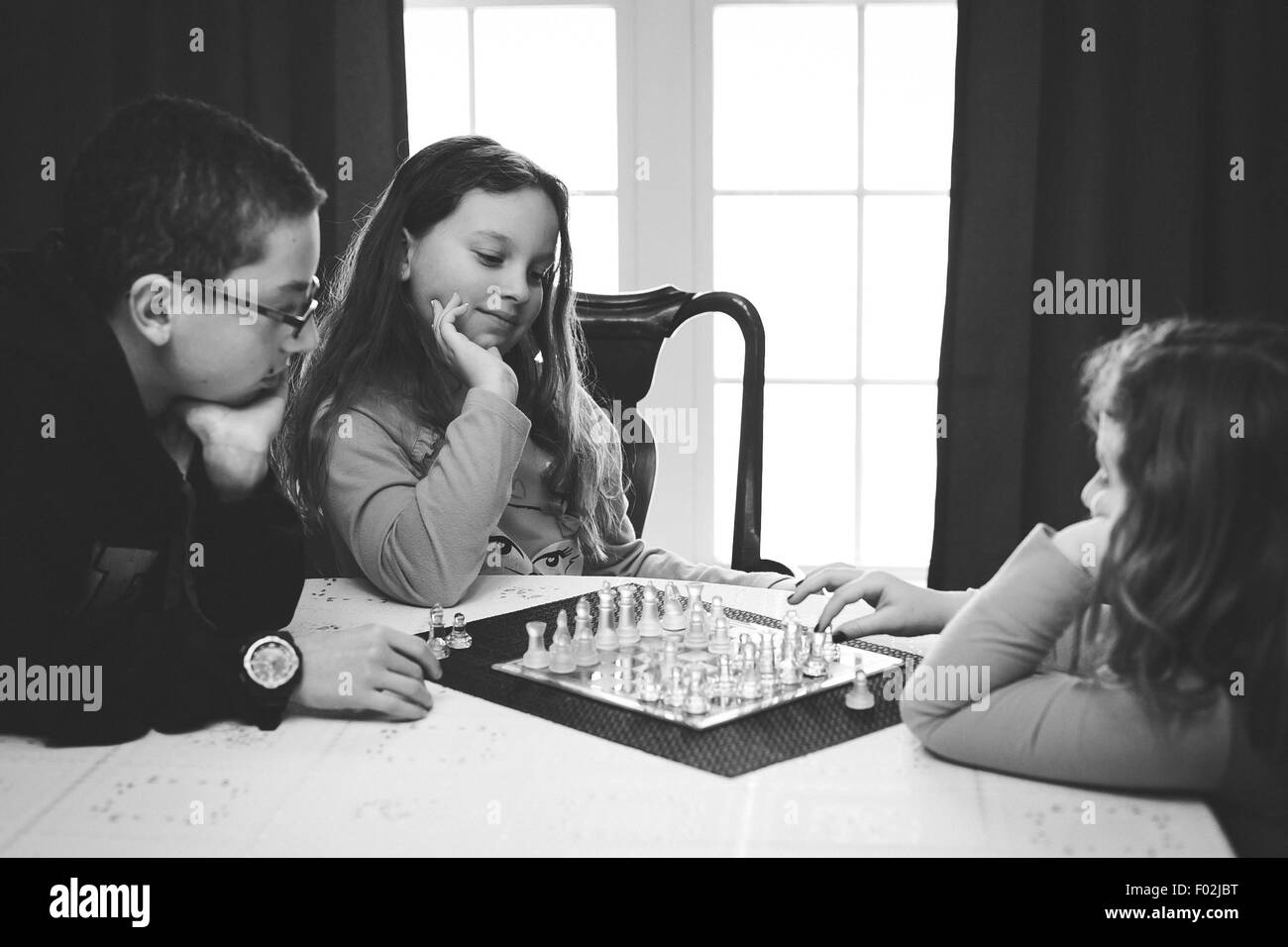 Three children playing a game of chess - Stock Image