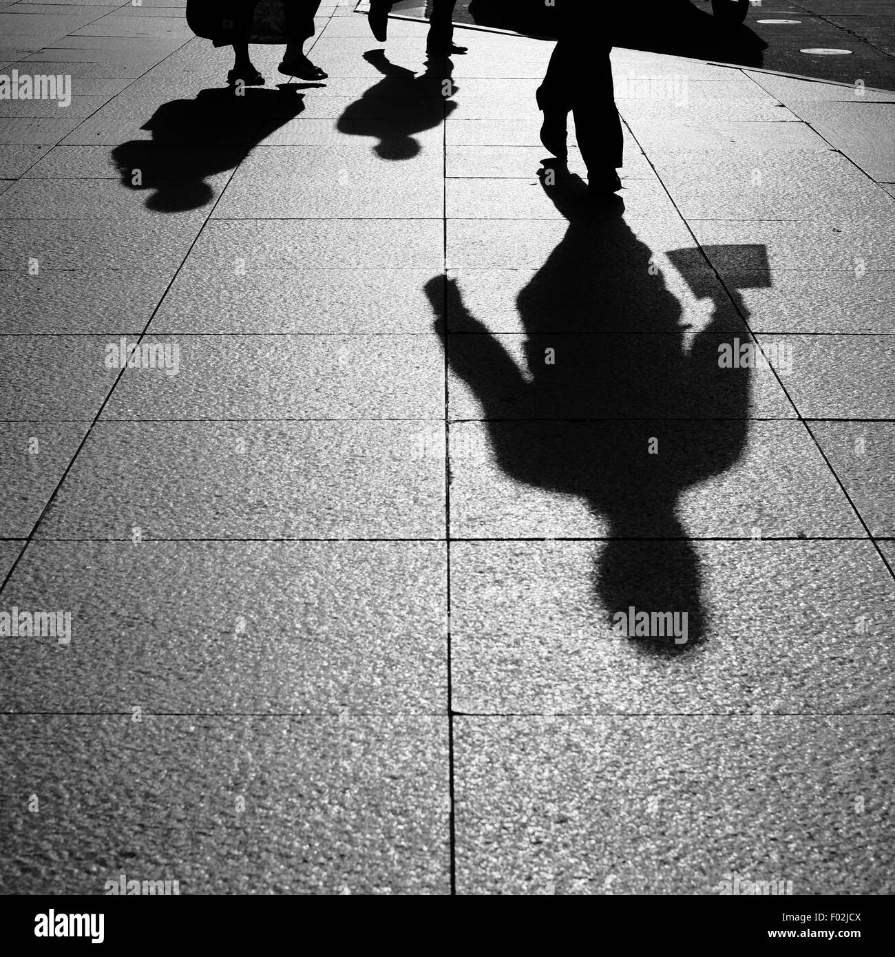 Shadows and Silhouettes of people walking on street in city - Stock Image