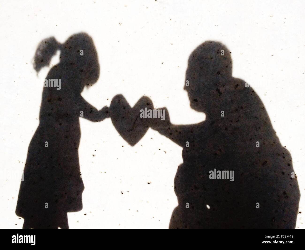 Shadow of a girl handing her father a heart - Stock Image