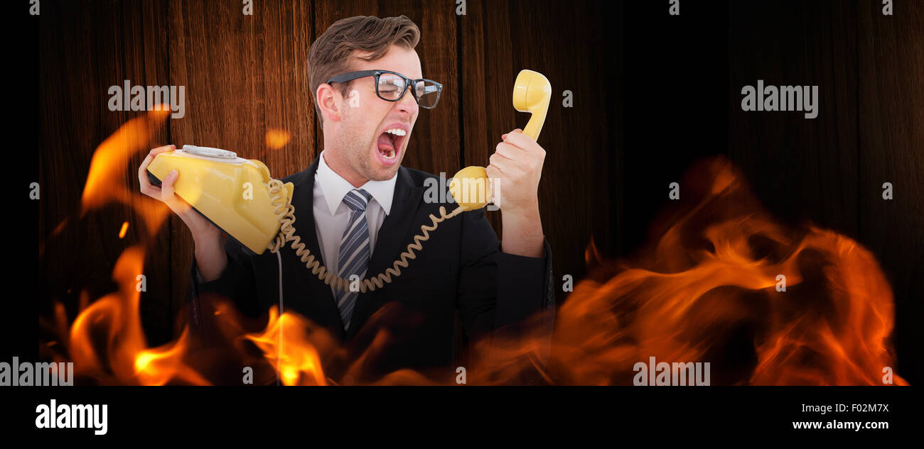 Composite image of geeky businessman shouting at telephone - Stock Image