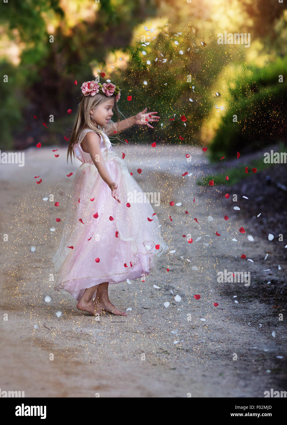 girl dancing on a dirt road surrounded by glitter and rose petals - Stock Image
