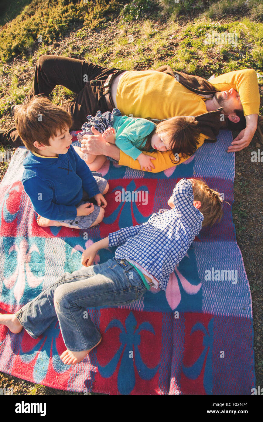 Father and three children lying on picnic blanket - Stock Image