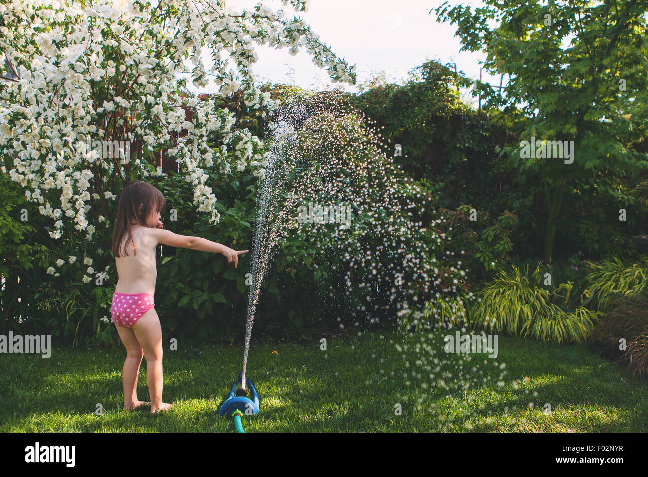 Girl playing with hosepipe in the garden - Stock Image